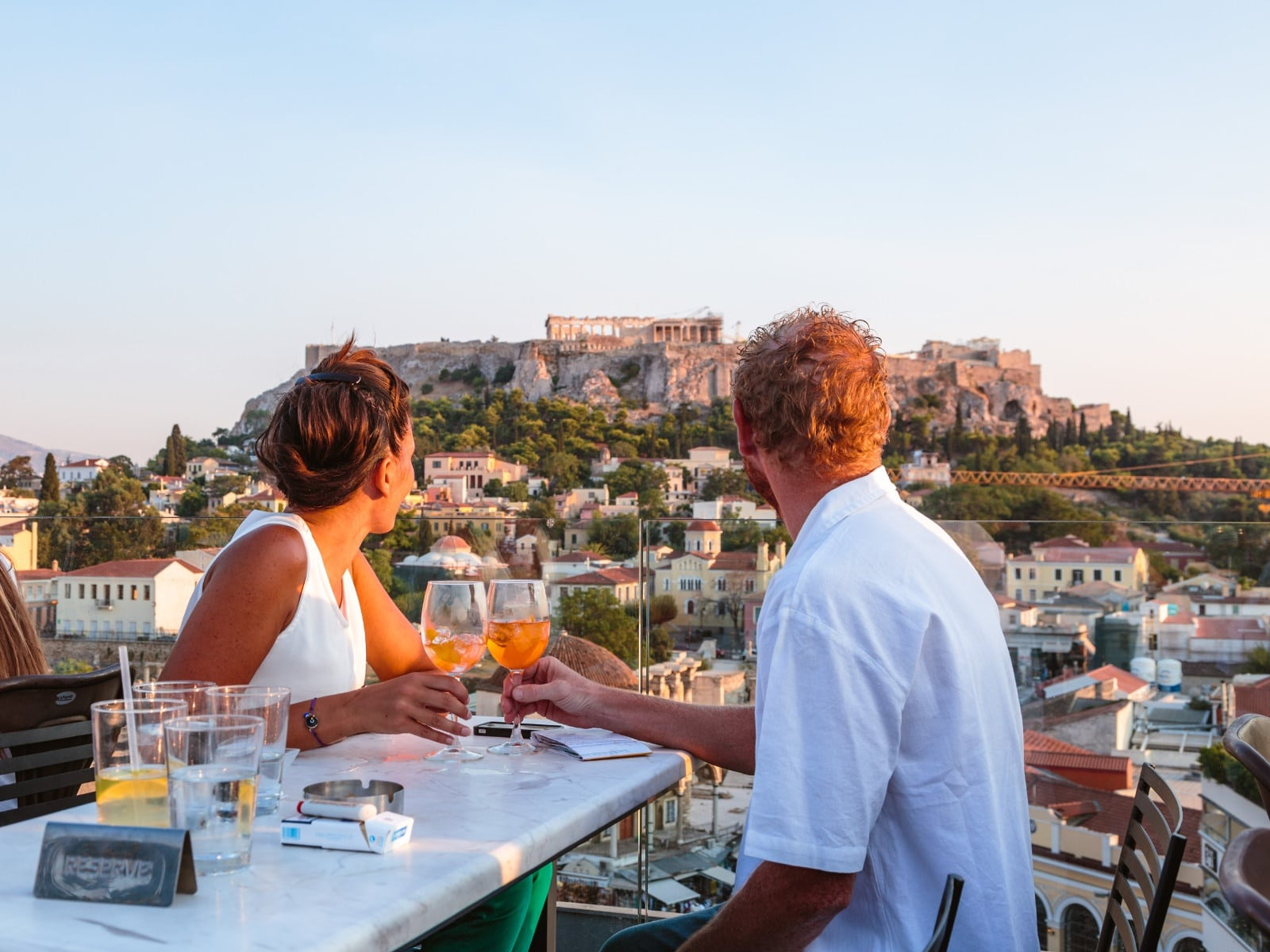 Couple Drinking And Enjoying The View Of The Acropolis At Sunset. Athens, Greece